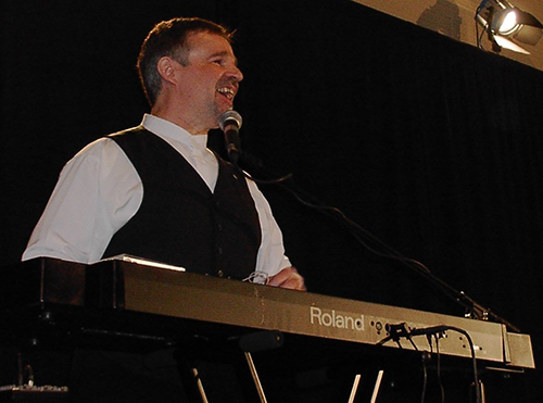 Photo of Terry Kelly performing and playing a keyboard